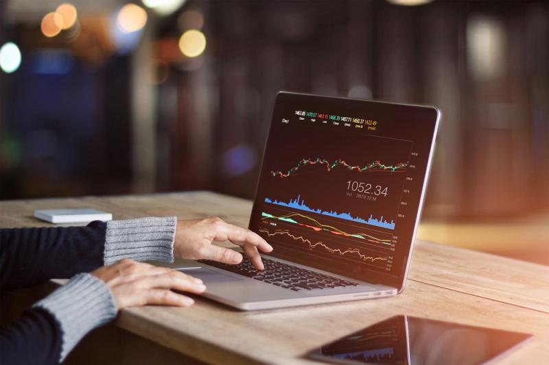 Man on laptop forex trading graph