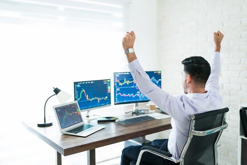 Freelance stockbroker celebrating win on multiple latptops
